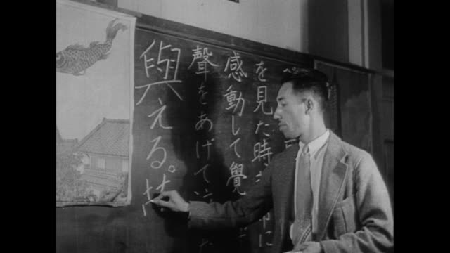 vídeos de stock, filmes e b-roll de suited japanese man writes in japanese on chalk board in the us during wwii - guerra do pacífico
