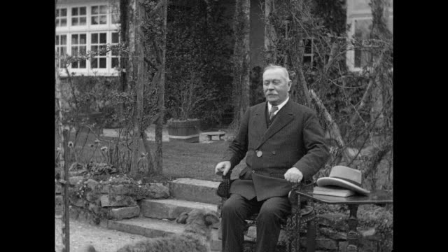 1925 suited older man sits down in garden with dog - 1925 stock videos & royalty-free footage