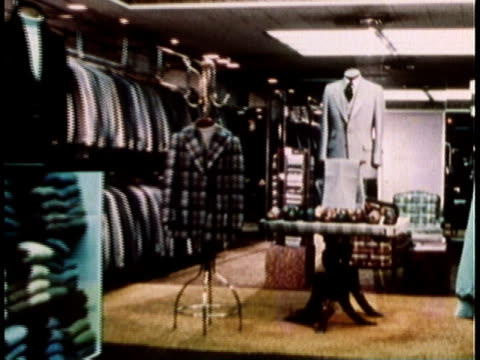 stockvideo's en b-roll-footage met 1979 montage suits and shirts on display and hanging from racks in men's clothing store / united states - herenkleding