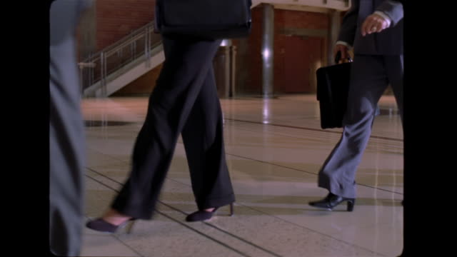 Suits, high heels and briefcases move across the lobby of an office-building.