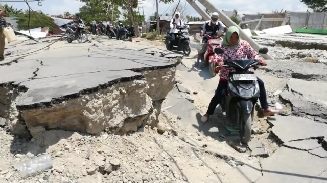 un says 200000 survivors in disaster zone need aid indonesia sulawesi palu sigi ext people on motorbikes along over destroyed road partially... - indonesia earthquake stock videos & royalty-free footage