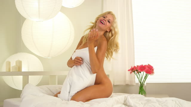 Sultry blonde woman in bed room
