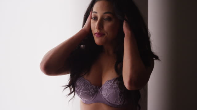 vídeos de stock, filmes e b-roll de sultry woman standing in lingerie by window - soutien