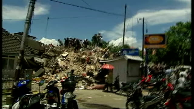 Sumatra Padang EXT Fire engine along sirens sounding SOT Bulldozer clearing rubble of destroyed building Search and rescue teams and soldiers...