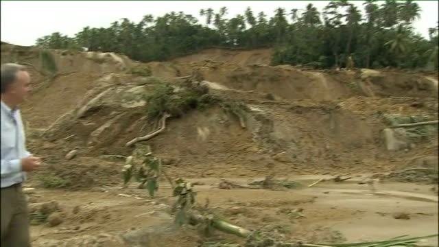 Sumatra Pulau Aiya EXT Torrential river flowing past destroyed area where split trunks of fallen trees lying in mud after earthquake disaster Rescue...