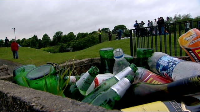 summer 2008 empty alcohol bottles and cans scattered on grass lager and beer bottles in bin man lying in drunken stupor as woman tries to rouse him... - trattenere video stock e b–roll