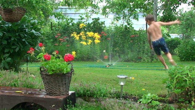 Summer. Boy having fun with garden sprinkler.