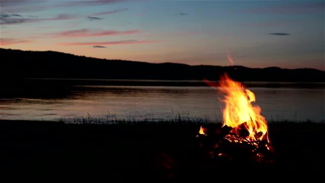 vídeos de stock e filmes b-roll de fogueira de acampamento de verão e lago ao pôr do sol - fogueira de acampamento