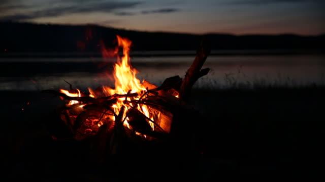 vídeos de stock, filmes e b-roll de fogueira de acampamento de verão e lago ao pôr do sol - firewood