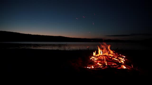 sommaren lägereld och sjön vid solnedgången - lägereld bildbanksvideor och videomaterial från bakom kulisserna