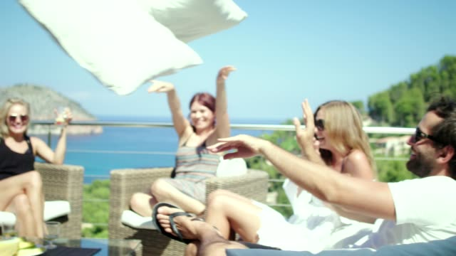 Summer coffee break on a terrace. Pillow fight