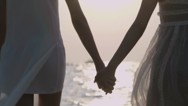 Summer couple lesbian holding hands at sunset on beach. Romantic couple women enjoying sun, sunshine, romance and love by the sea. Couple on summer vacation travel holiday.LGBT Vacation.LGBT concept.