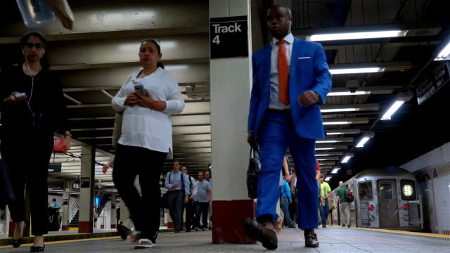 Summer evening rush hour commuters at the Grand Central Station shuttle subway train platform / Grand Central Station Subway lines here include the 4...