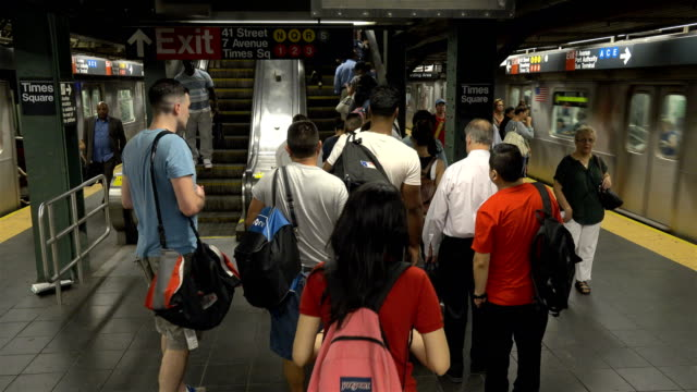 summer evening rush hour commuters on the number 7 subway platform in times square / connections to trains 1 3 a, e, n, q, c, r trains and the port... - 42nd street stock videos & royalty-free footage