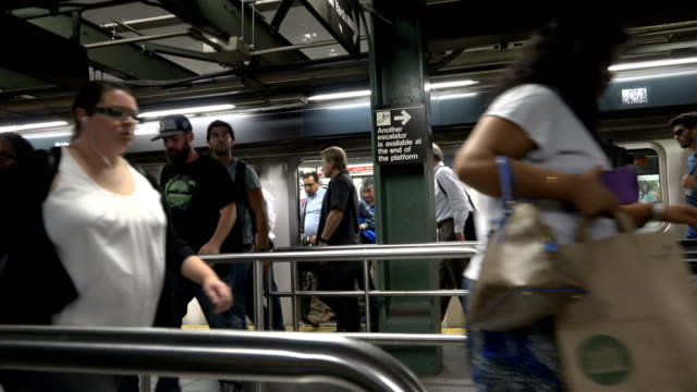 summer evening rush hour commuters on the number 7 subway platform in times square / connections to trains 1 3 a e n q c r trains and the port... - 42nd street stock videos & royalty-free footage
