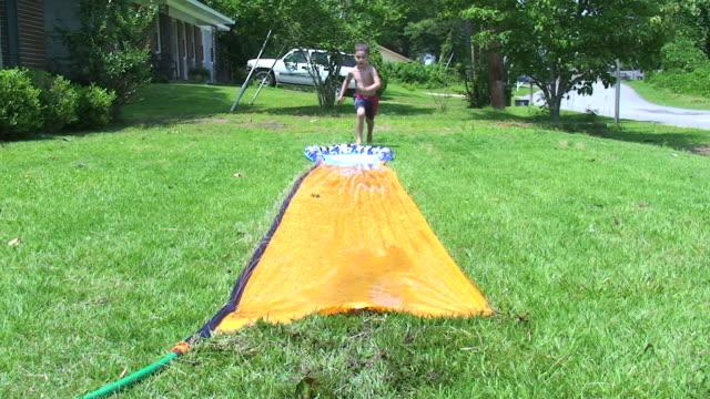 summer fun outdoors - water slide stock videos & royalty-free footage
