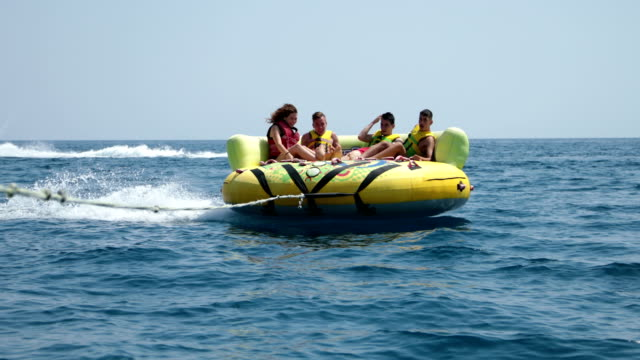 summer fun.four friends enjoying an inflatable tube ride at sea - water sport stock videos & royalty-free footage