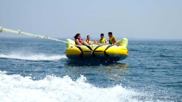summer fun.four friends enjoying an inflatable tube ride at sea - inner tube stock videos and b-roll footage