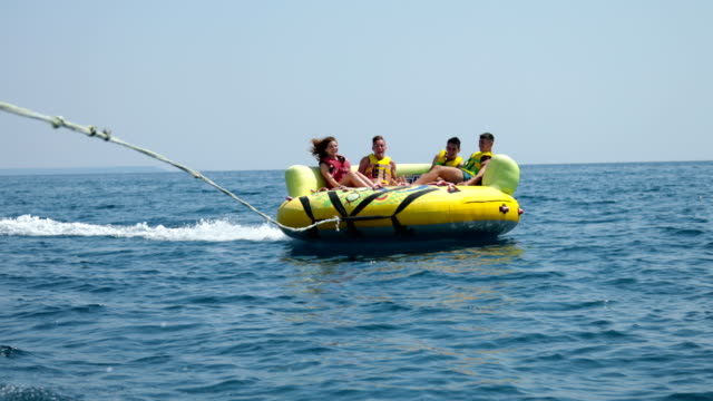 vídeos de stock e filmes b-roll de summer fun.four friends enjoying an inflatable tube ride at sea - boia equipamento de desporto aquático