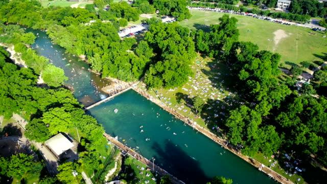 summer heat brings huge crowds swimming at barton springs pool in austin , texas - standing water stock videos & royalty-free footage