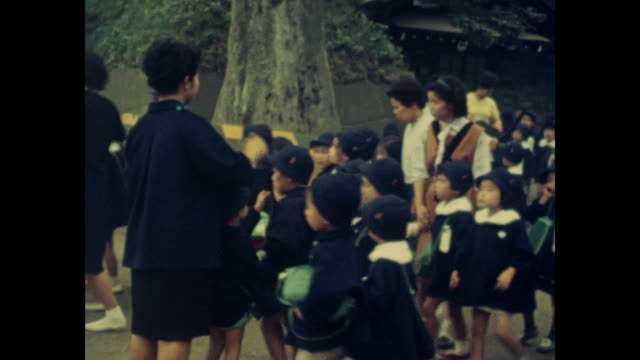 summer in tokyo while the olympic games 1964 group of kids of a primary school or kindergarten with their teacher all wearing uniforms / 1209001 - japanese school uniform stock videos & royalty-free footage