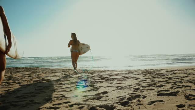 Summer is here: bikini surfer girls at sea