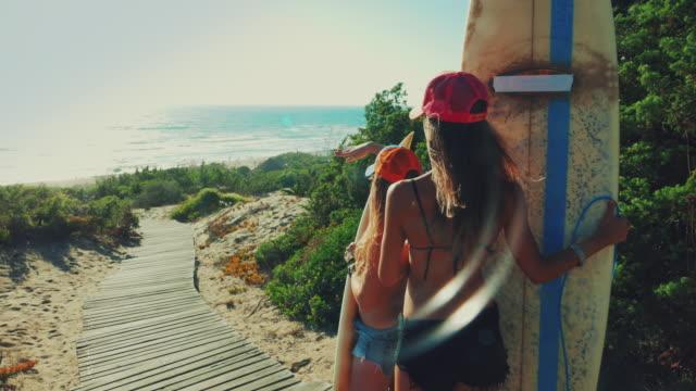 vídeos de stock, filmes e b-roll de o verão está aqui: meninas surfistas observa o mar - arrebentação