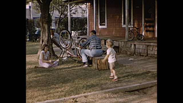 1957 summer -man fixes bicycle while children watch - repairing stock videos & royalty-free footage