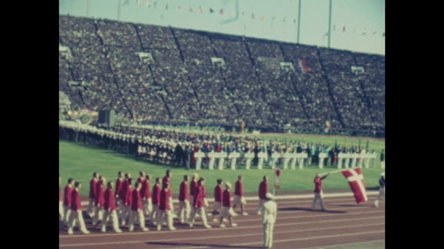 vídeos de stock e filmes b-roll de summer olympic games tokio 1964 national stadium day of the opening ceremony filmed out of the audience athletes of all nations are marching in... - 1964