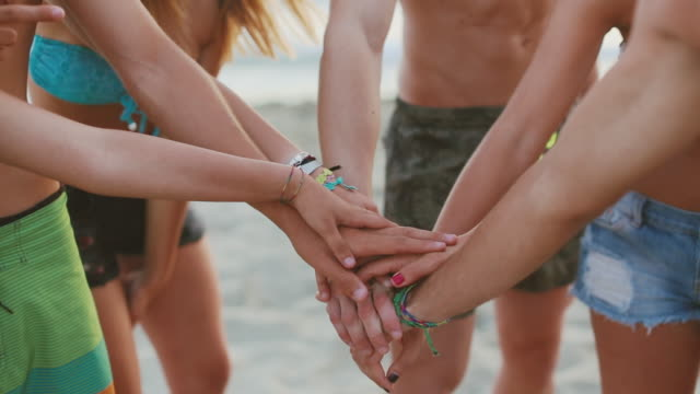 summer people: oath pile of hands on the beach - agreement stock videos & royalty-free footage