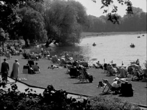 people relax around lake in park england ext general view people relaxing in the sunshine around boating lake in park broadcast at 830pm - sunshine lake bildbanksvideor och videomaterial från bakom kulisserna