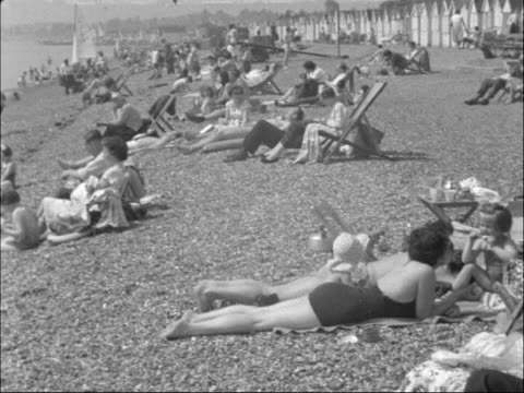people relaxing on the beach england ext general view people relaxing on pebble beach sunbathing in swimming costumes sitting in deckchairs broadcast... - swimming costume stock videos and b-roll footage