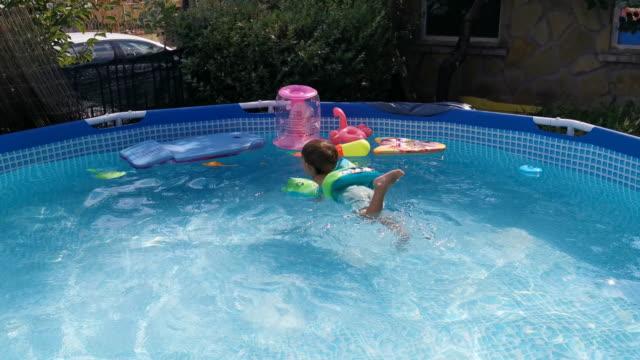 sommar nöjen i trädgården. barn som simmar i poolen på bakgården. - utebassäng bildbanksvideor och videomaterial från bakom kulisserna