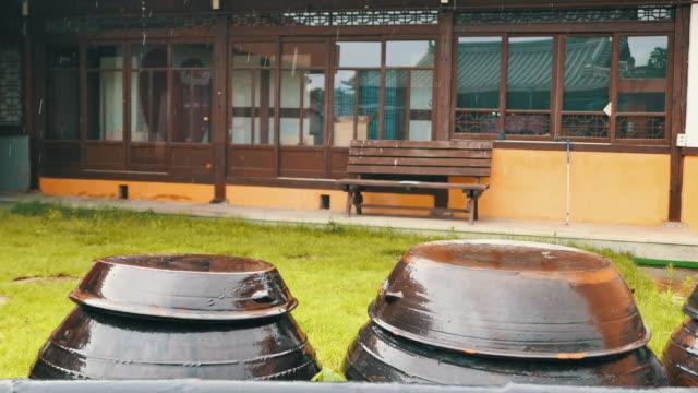vidéos et rushes de summer rain falling on jangdokdae (korean earthen jar stand) in jeonju hanok village / jeonju-si, jeollabuk-do, south korea - plaque de montage fixe