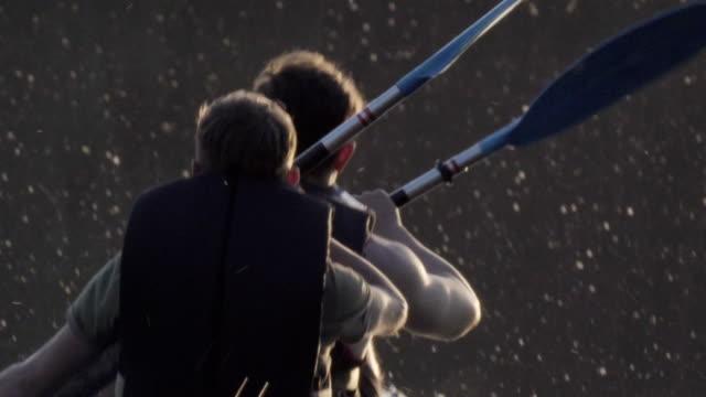 vídeos y material grabado en eventos de stock de verano relajante actividad. dos amigos en kayak en el lago - remar