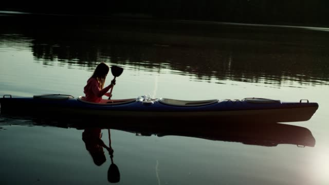 summer relaxing activity. young man kayaking on the lake - remare video stock e b–roll