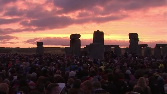 vídeos y material grabado en eventos de stock de summer solstice at stonehenge; england: wiltshire: stonehenge: ext various shots sun rising over stonehenge with crowd of people present - solsticio de verano