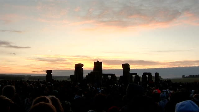 vídeos y material grabado en eventos de stock de summer solstice celebrations at stonehenge; druid chatting to others by stone circle / shots of crowds of people gathered by stonehenge for sunrise,... - solsticio de verano