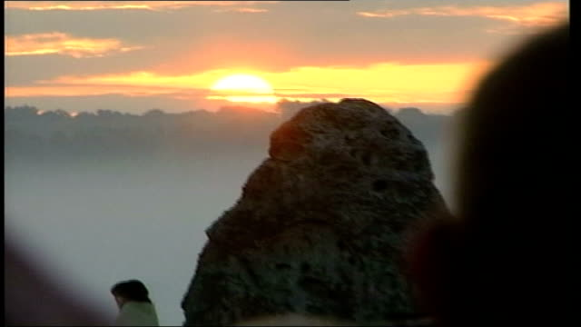 sunrise at stonehenge; itn england: wiltshire: stonehenge: ext/day gvs people gathered round stones as sun rises over stone, people cheering &... - solstice stock videos & royalty-free footage