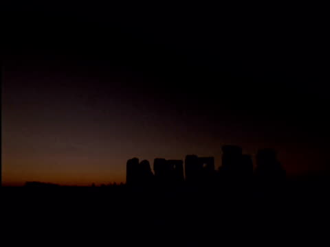 Summer solstice sunrise over Stonehenge and crowds Wiltshire