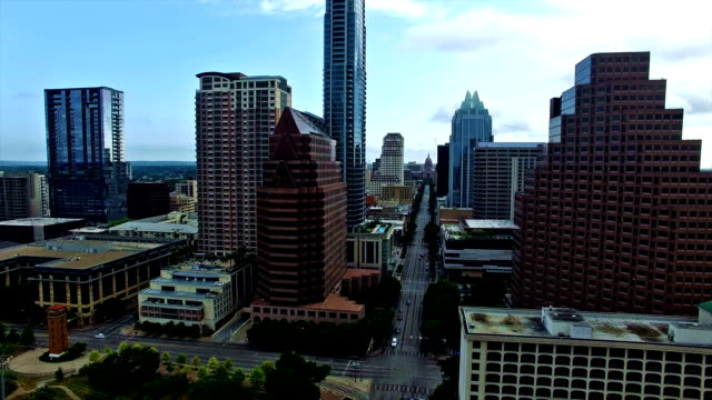 summer sunrise close to downtown skyscrapers aerial over austin texas congress avenue iconic landmark view from the air 4k - texas state capitol building stock videos & royalty-free footage