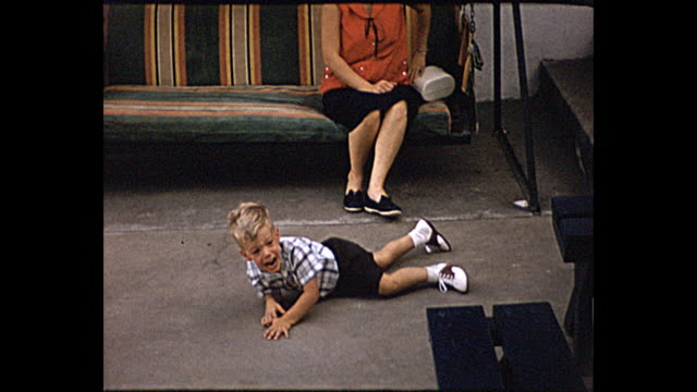 vidéos et rushes de 1957 summer - toddler boy having a tantrum mother watches him and comforts him - displeased