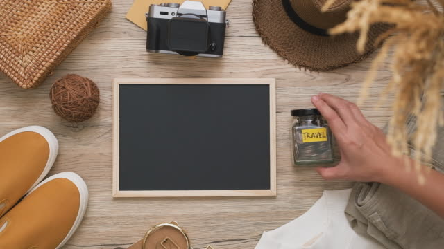 summer travel flat lay of traveller accessories set and blackboard with hand put down budget travel on wooden table with copy space - flat lay stock videos & royalty-free footage
