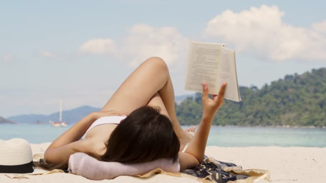 summer vacation asian woman reading a book on the beach in free time holiday - book stock videos & royalty-free footage
