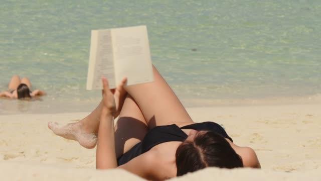 Vacances d'été femme asiatique lisant un livre sur la plage en vacances de temps libre