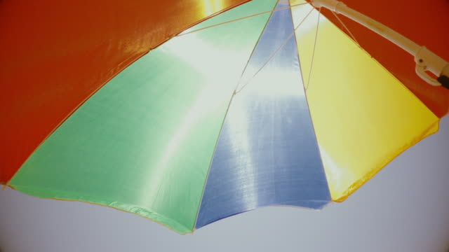 vídeos de stock e filmes b-roll de summer vacations symbol: multi colored beach umbrella parasol protecting against the sun - com sombra