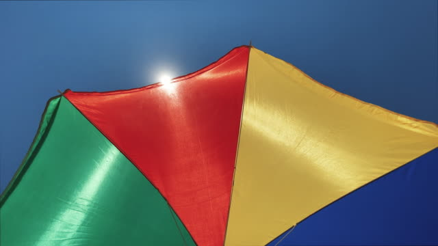 summer vacations symbol: multi colored beach umbrella parasol protecting against the sun - parasol stock videos & royalty-free footage