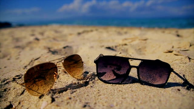 Summer vacations,sunglasses on the sand beach ,b roll