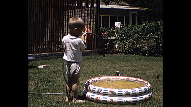 1957 Summer - young boy in backyard pouring water in inflatable pool