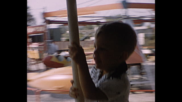 1957 Summer  -young boy in merry go round father takes pictures of him